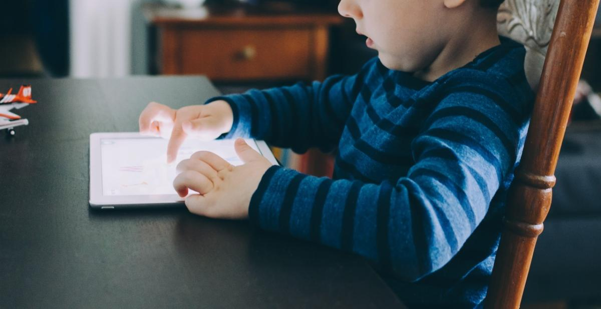 A young child uses an iPad while sitting at a dining room table.