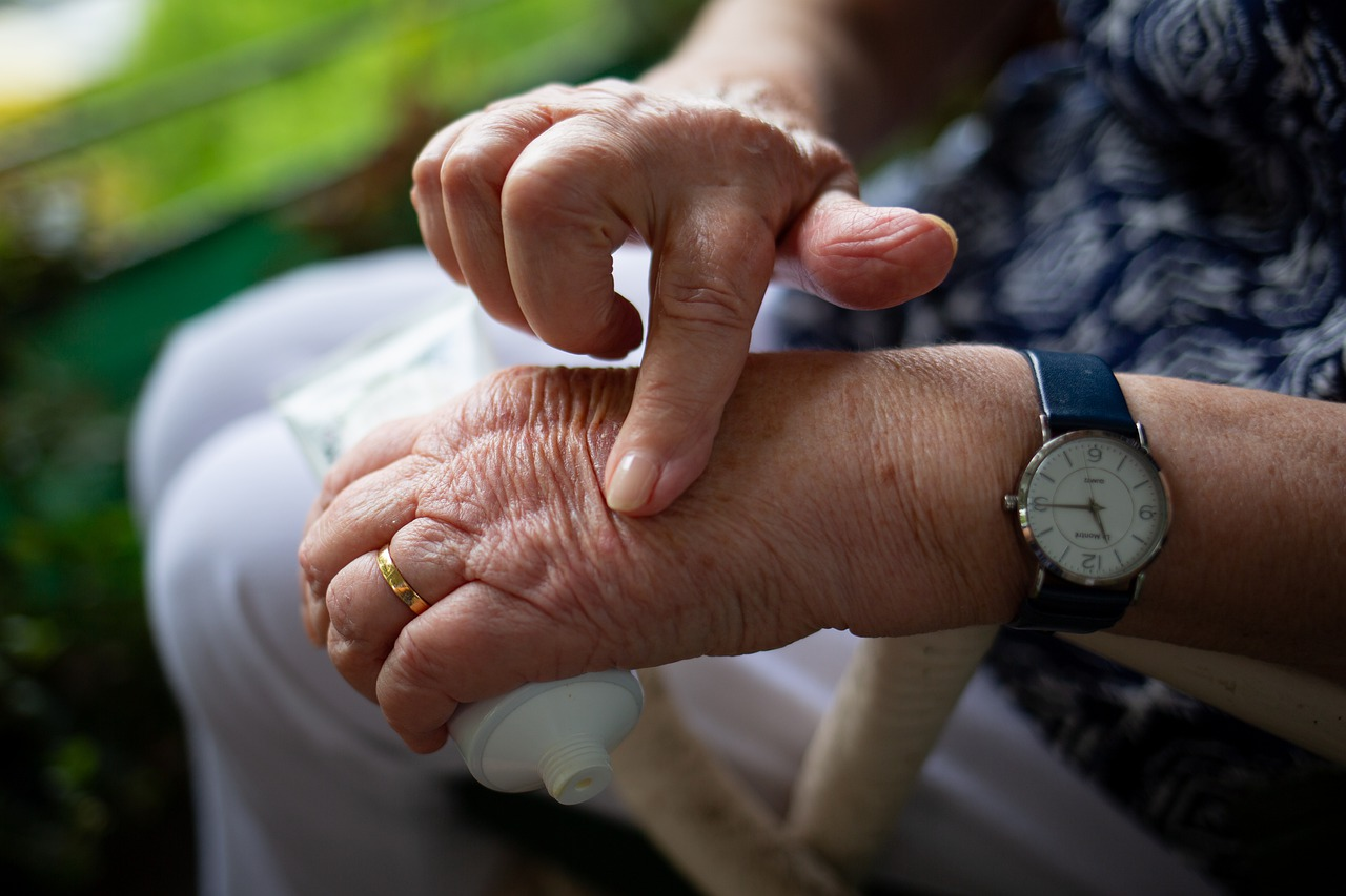 An elderly woman applies a cream to her hands