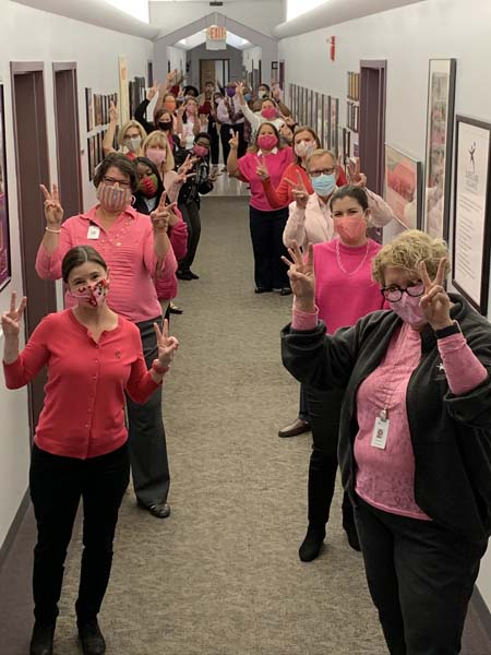 LifeCare Alliance employees posing in pink clothing in honor of Breast Cancer Awareness Month