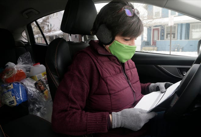 Volunteer looks over Senior PetCare AniMeal route sheet in car.