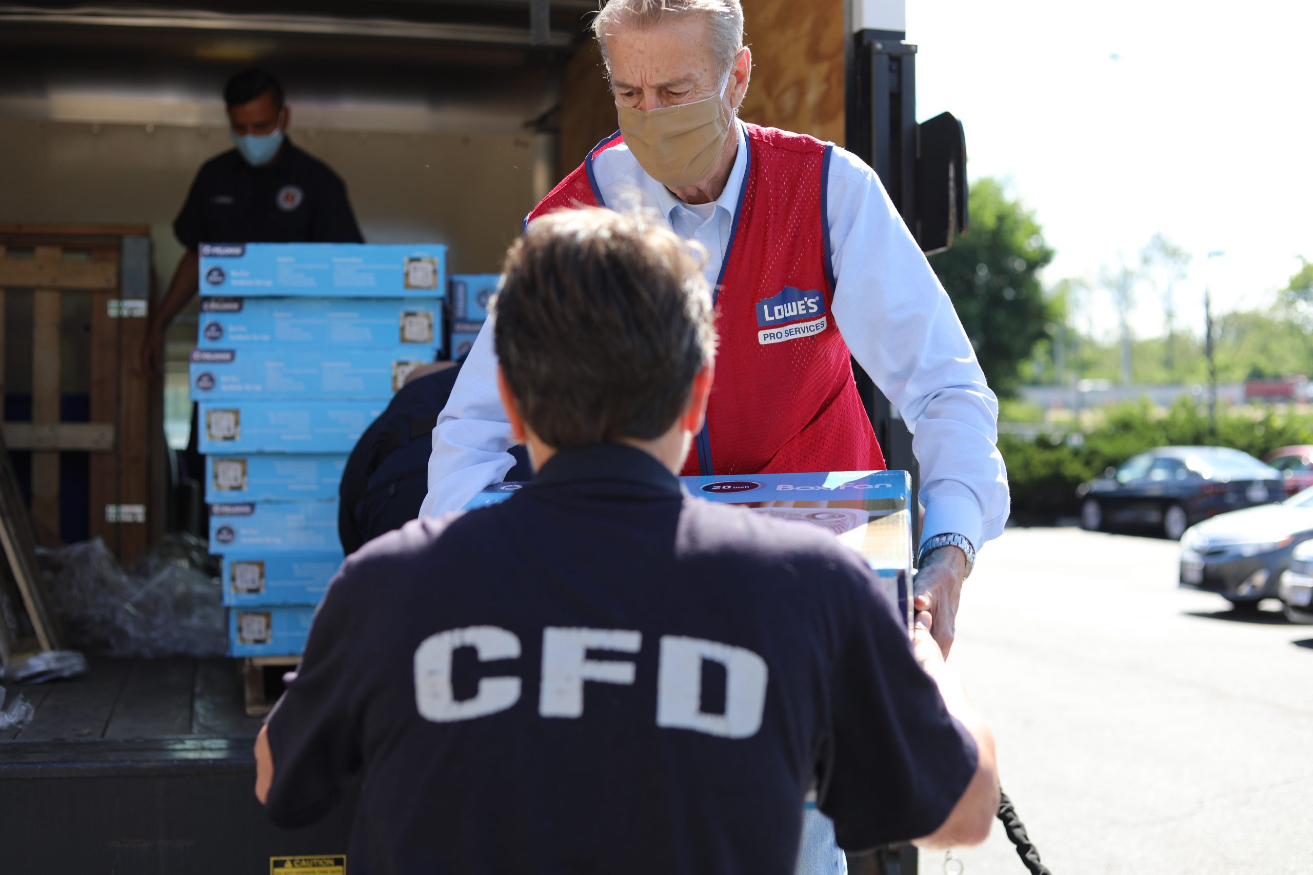 A Lowe's employee hands off a stack of fans to a Columbus firefighter.